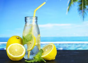 A glass of lemon water with 3 lemons around the glass and the beach as a background
